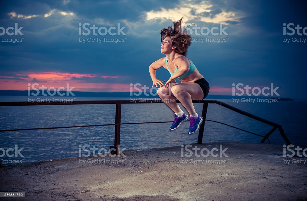 Young woman in sportswear exercising on pier stock photo
