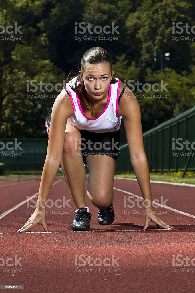 Young woman in sprinting position royalty-free stock photo