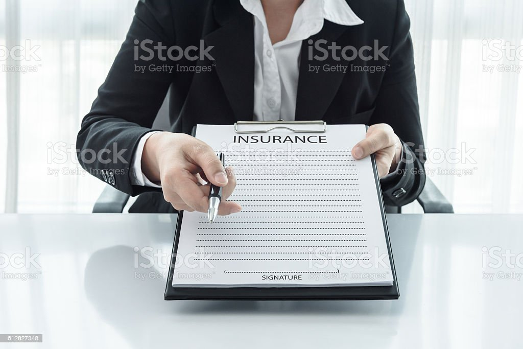 young woman in suit  her office showing an insurance policy stock photo