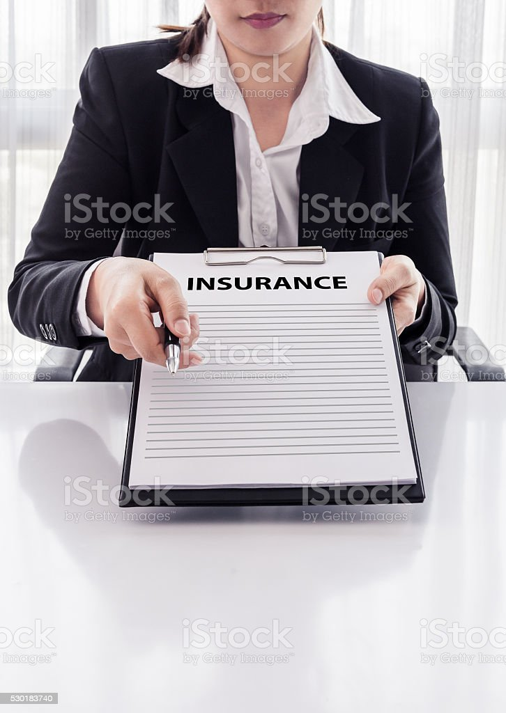 young woman in suit in his office showing insurance policy stock photo