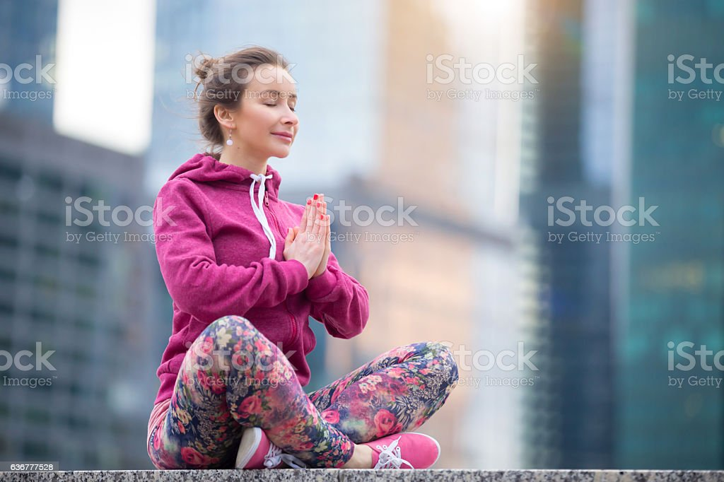 Young woman in Sukhasana pose against the city stock photo
