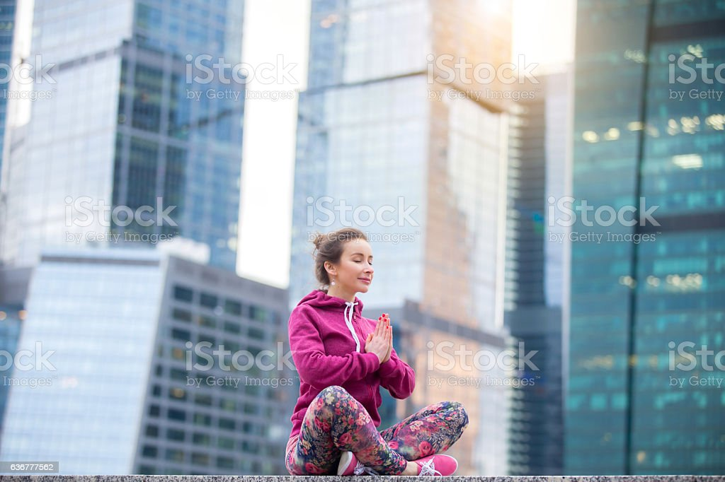 Young woman in Sukhasana pose against the skyscrapers stock photo
