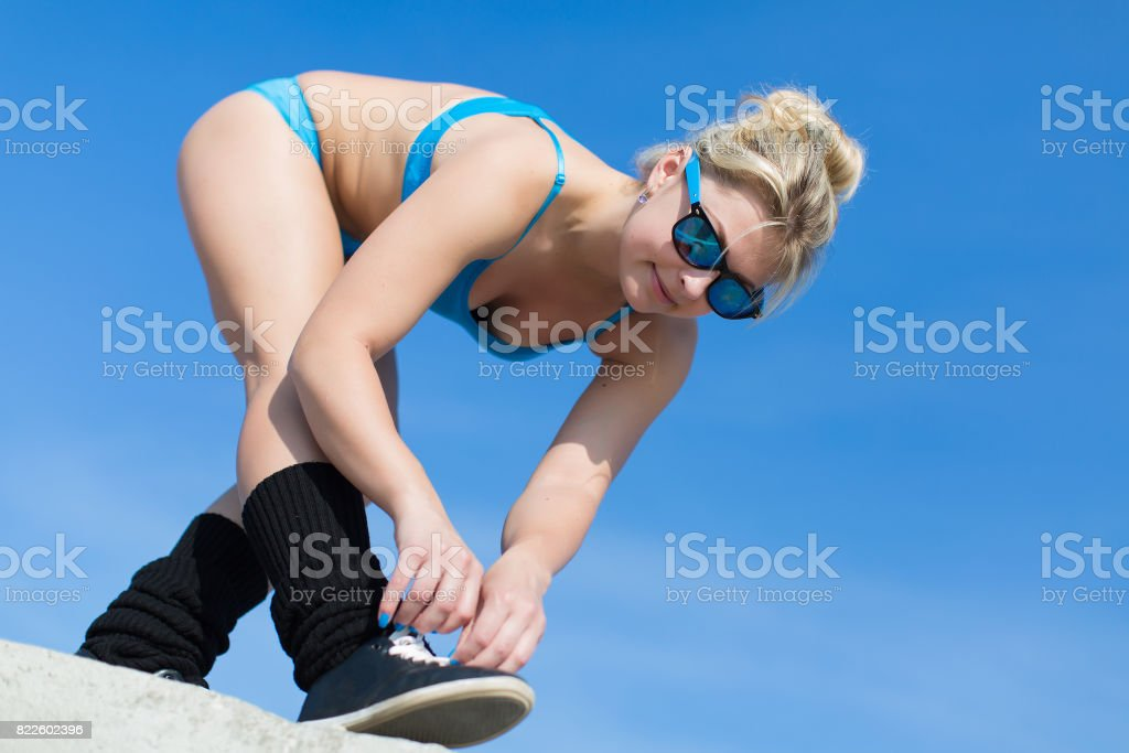 Young woman in sunglasses lace up her sneakers stock photo