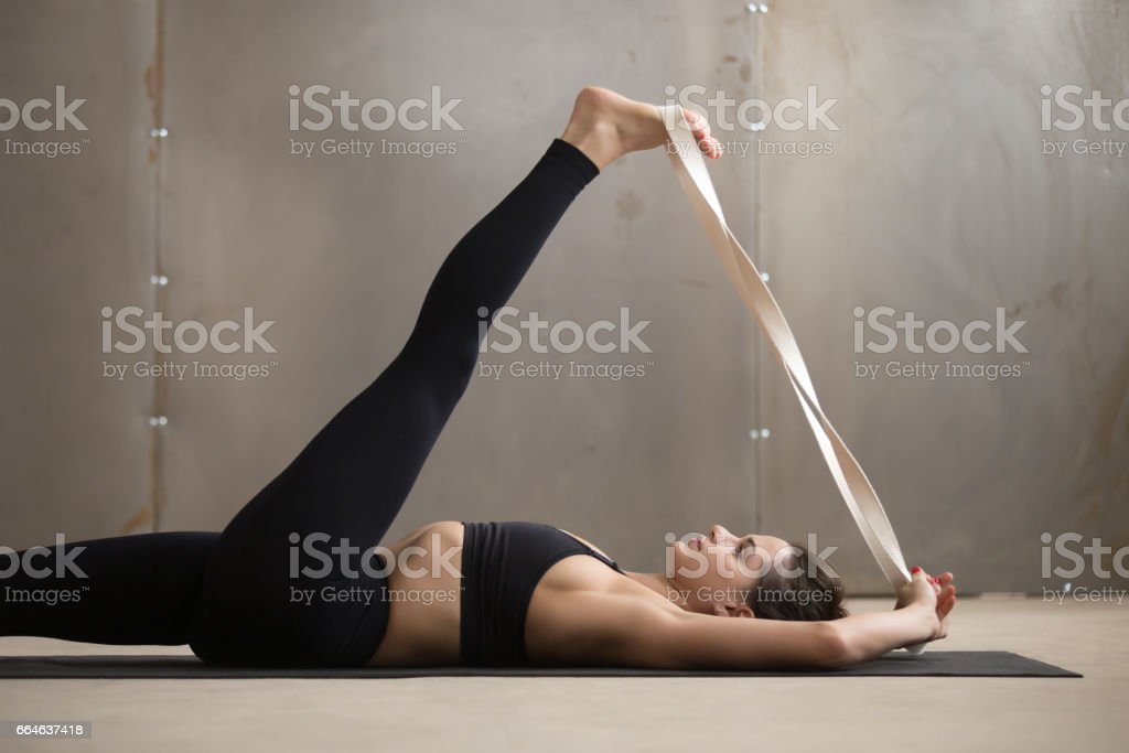Young woman in Supta Padangushthasana pose, grey studio backgrou stock photo