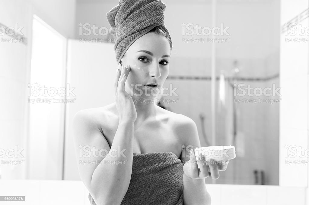 Young Woman in the Bathroom takes lotion o her Face stock photo