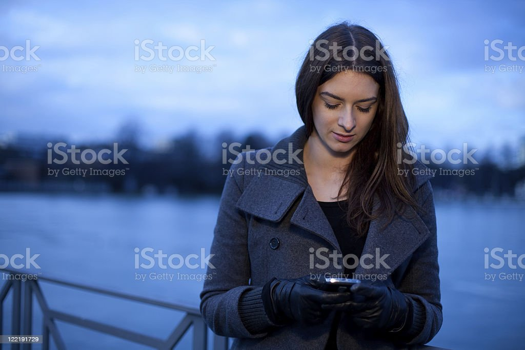 Young Woman In The City At Dusk With Mobile Phone royalty-free stock photo