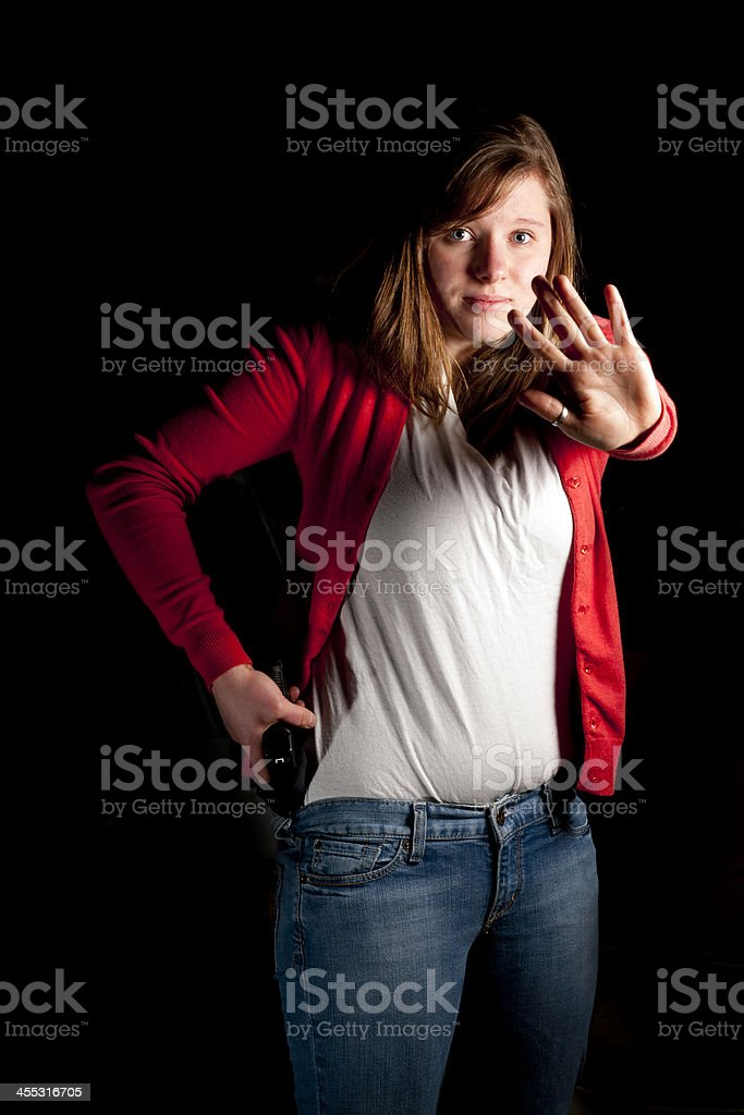 A young woman in the dark with her hand extended out  stock photo
