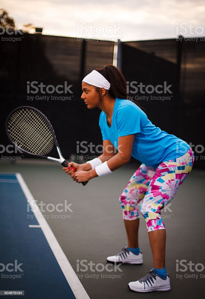Young woman in the ready position on tennis court stock photo