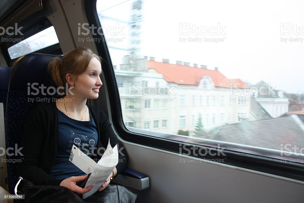 Young woman in the train looking through the window. stock photo