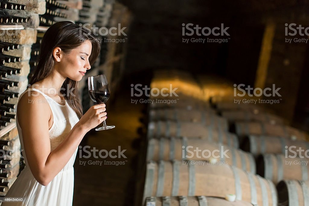 Young woman in the wine cellar stock photo