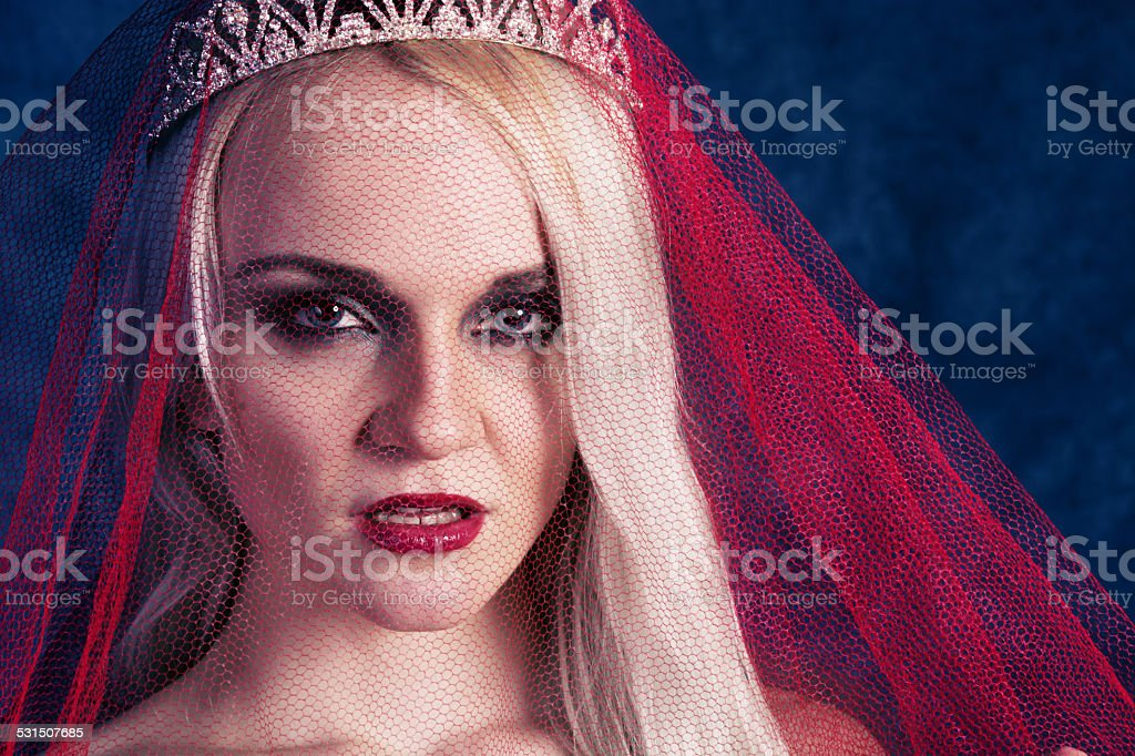 Young woman in tiara and red veil, glaring at camera. stock photo