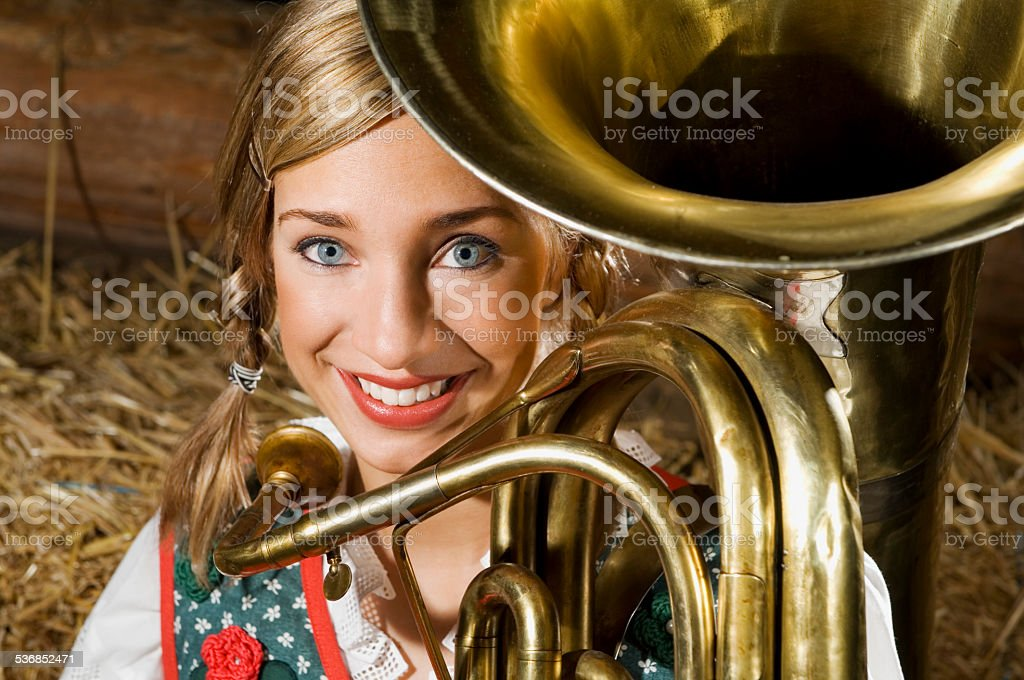 Young woman in traditional costume, with tuba, portrait stock photo