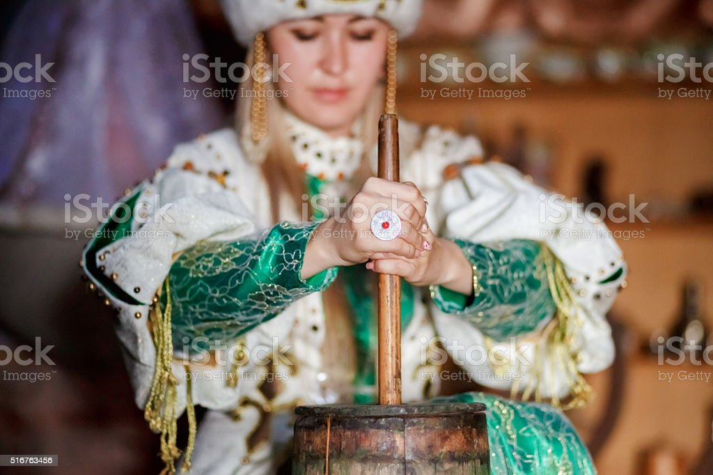 Young woman in traditional dress producing butter from milk at stock photo