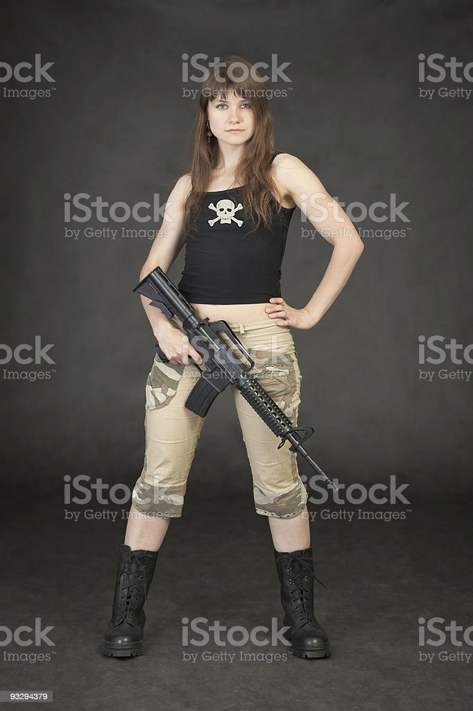 Young woman in trousers and boots with rifle royalty-free stock photo