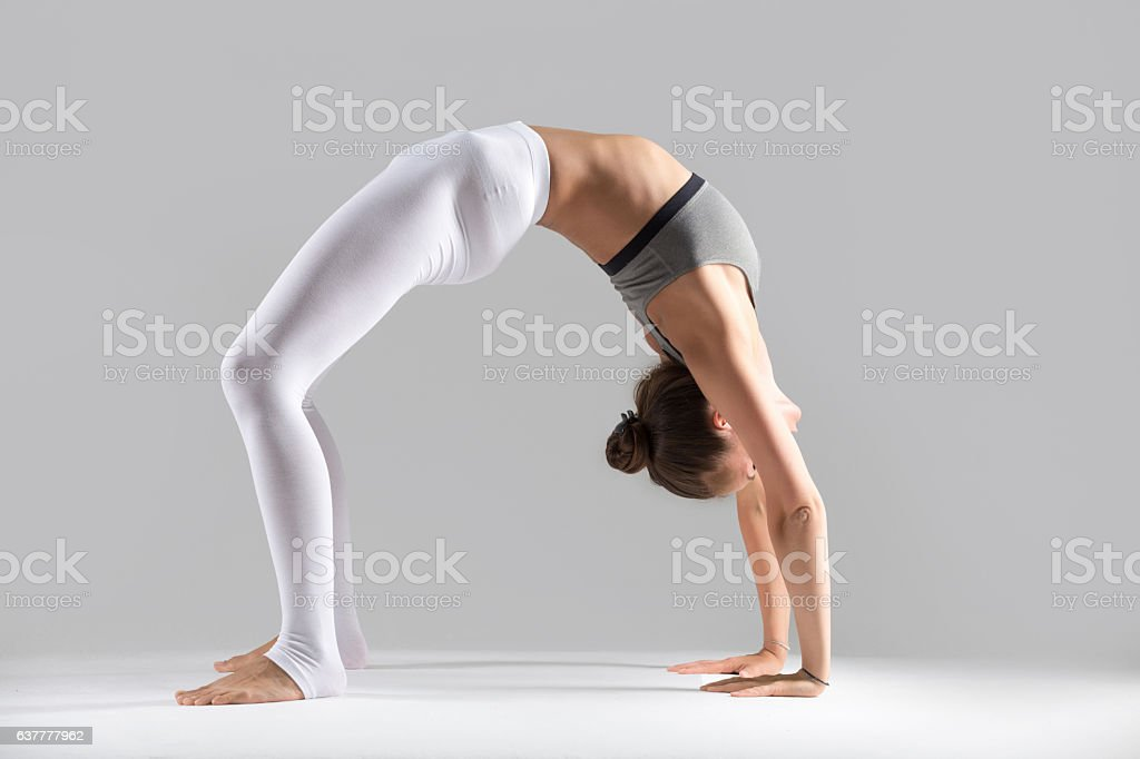 Young woman in Urdhva Dhanurasana pose, grey studio background stock photo