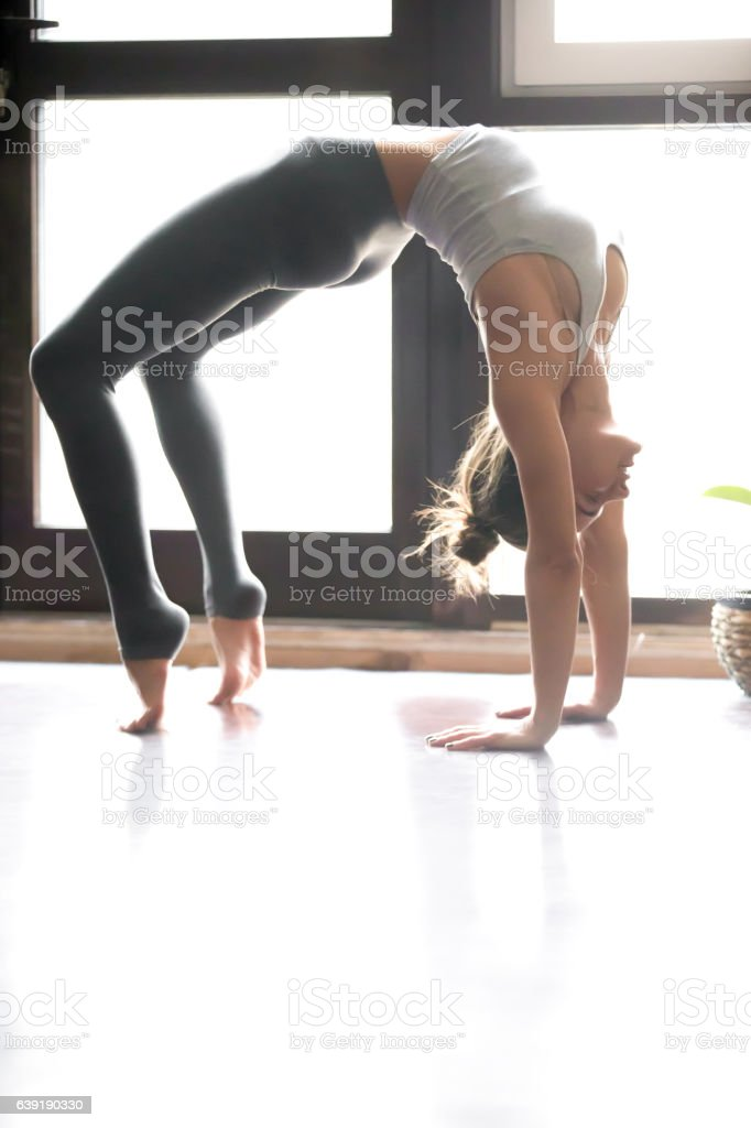 Young woman in Urdhva Dhanurasana pose, home interior background stock photo