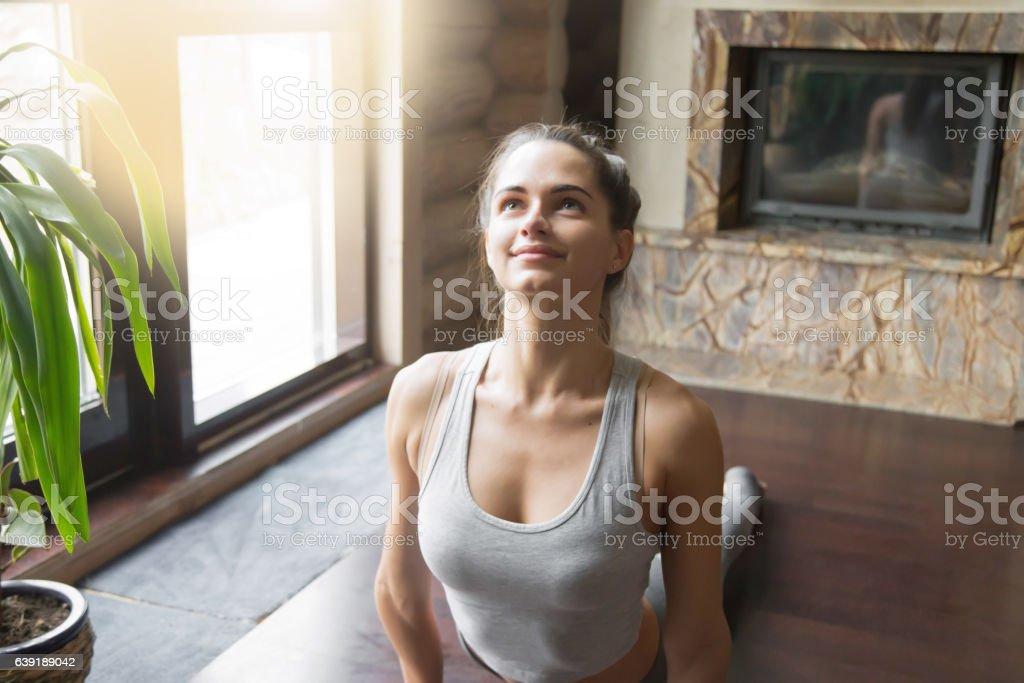 Young woman in Urdhva mukha shvanasana pose, home interior backg stock photo