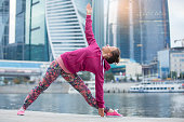 Young woman in Utthita Trikonasana pose against the skyscrapers