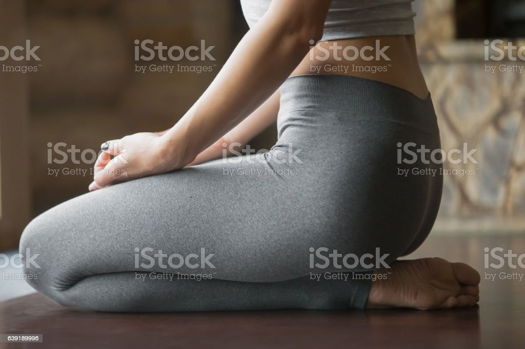 Young woman in vajrasana pose, home interior background, closeup stock photo