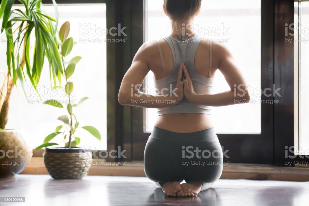 Young woman in vajrasana pose, home interior background, namaste stock photo