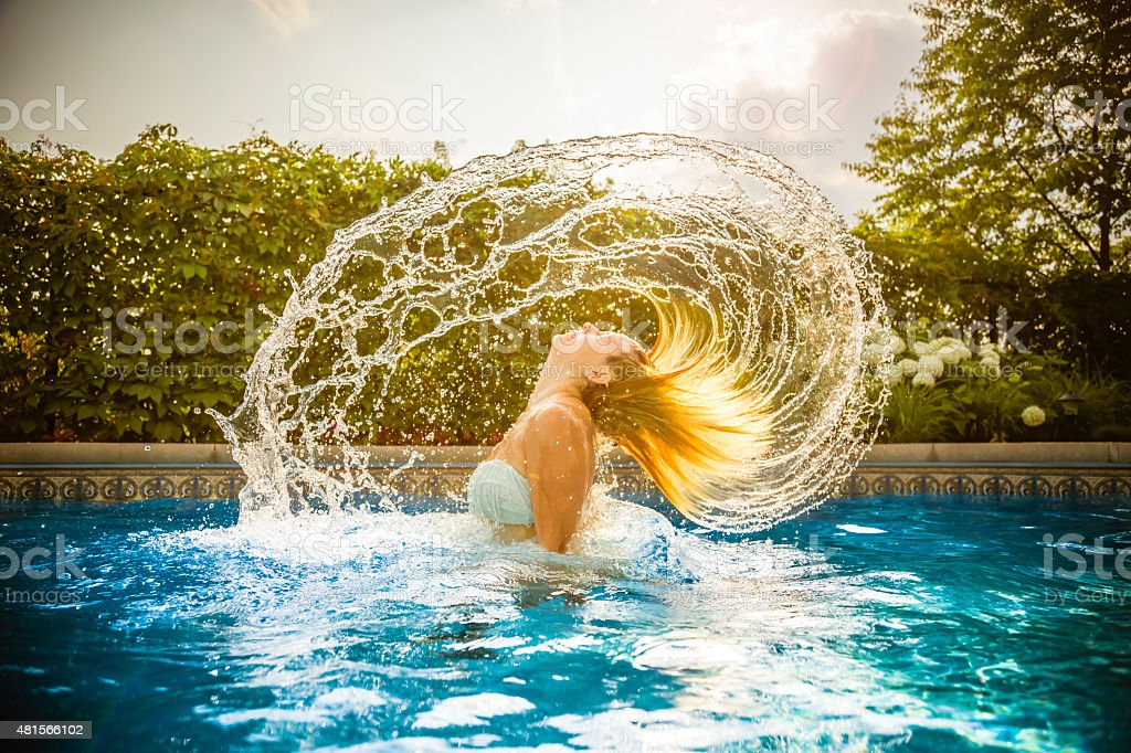 Young woman in water with hair splash stock photo