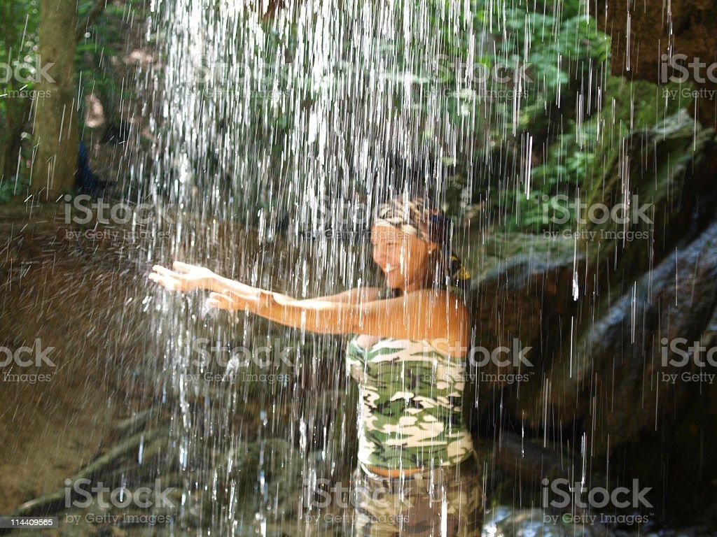 Young woman in waterfall stock photo