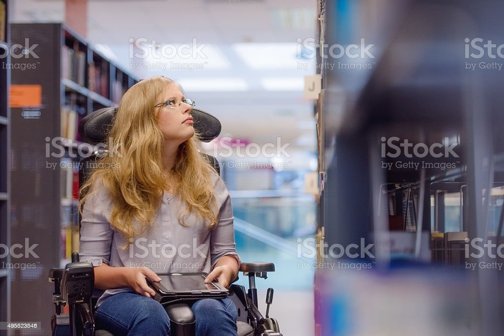 Young woman in wealchair in library stock photo