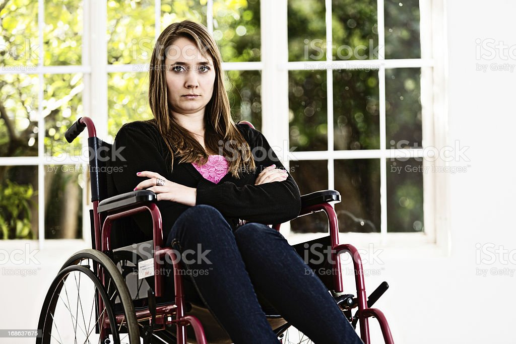 Young woman in wheelchair frowns unhappily stock photo