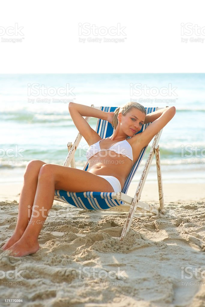 Young woman in white bikini by the shore on a deck chair stock photo