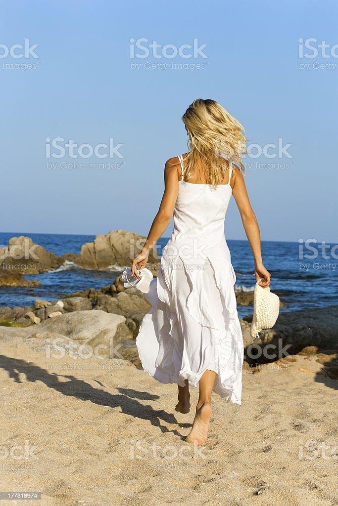 Jeune femme en robe blanche la course. photo libre de droits