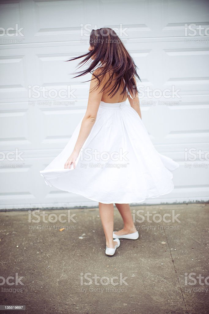 Young Woman in White Dress Spinning Around royalty-free stock photo