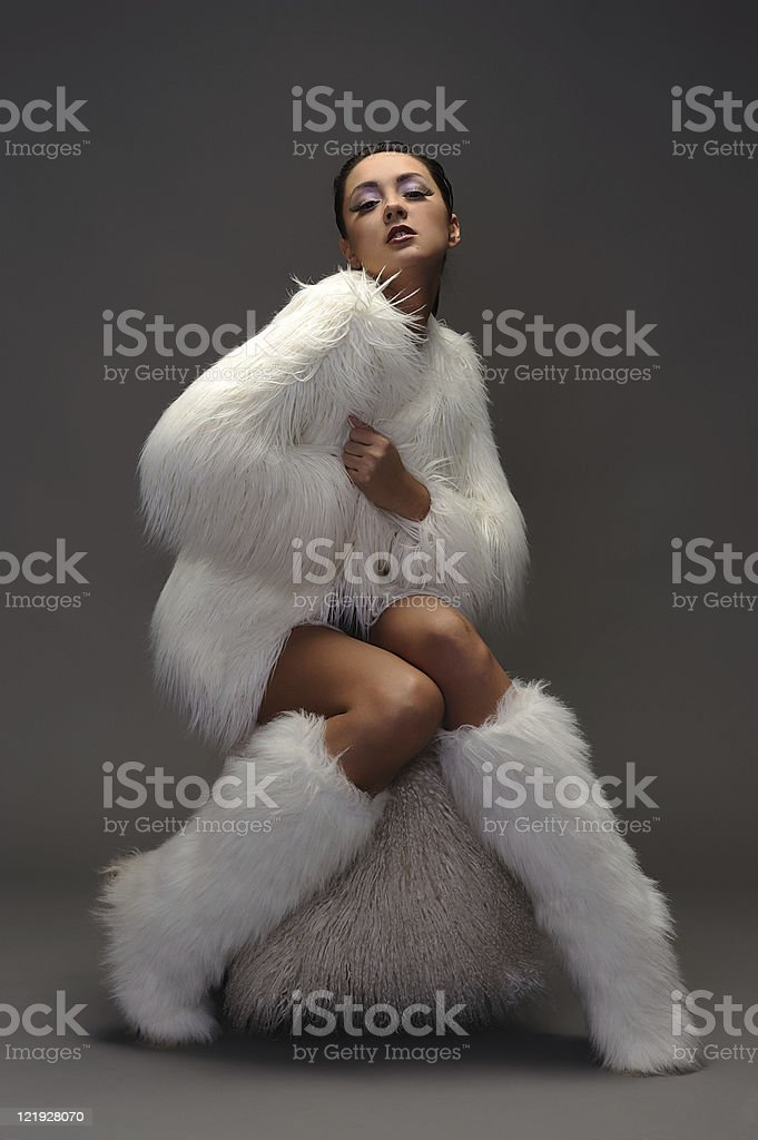 Young woman in white fur coat sitting on ottoman chair stock photo