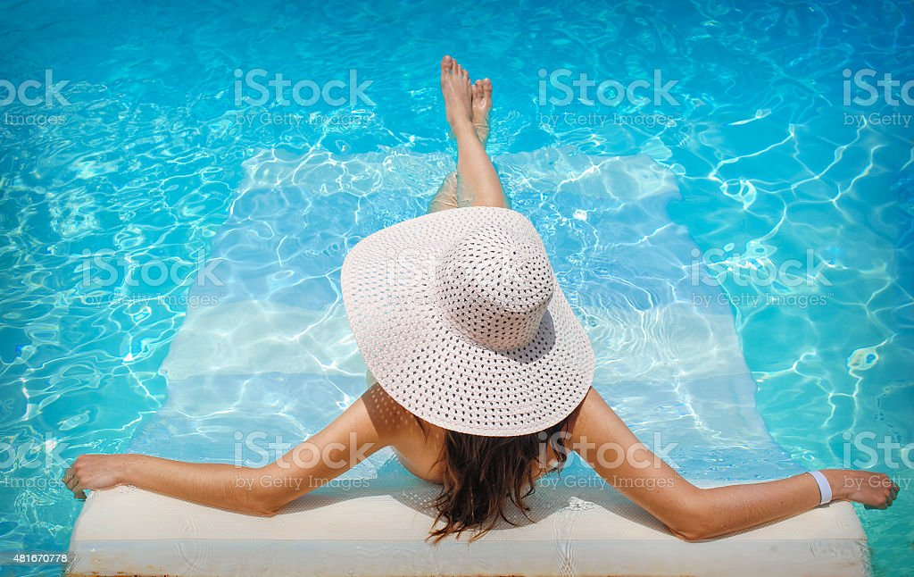 young woman in white hat resting in pool stock photo
