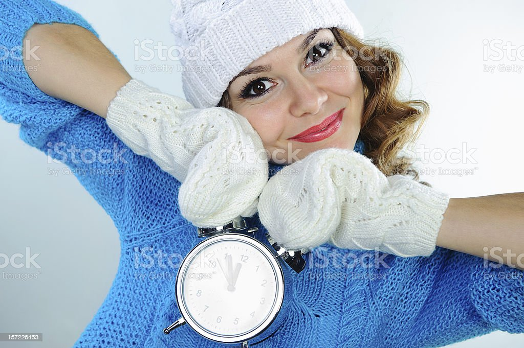 Young woman in winter clothes holding alarm clock royalty-free stock photo