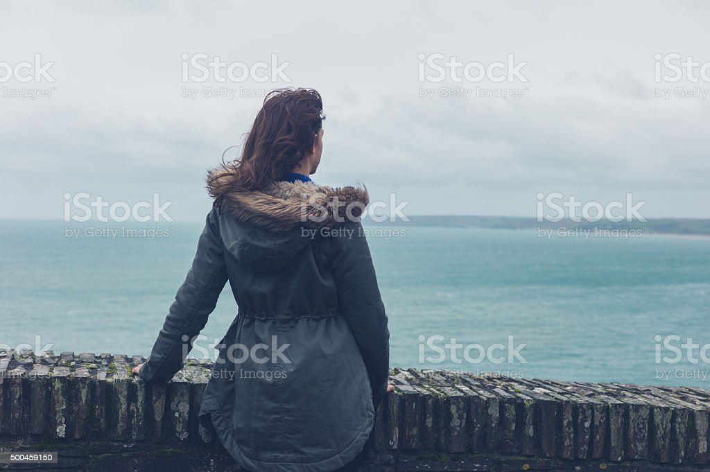 Young woman in winter coat by the sea stock photo