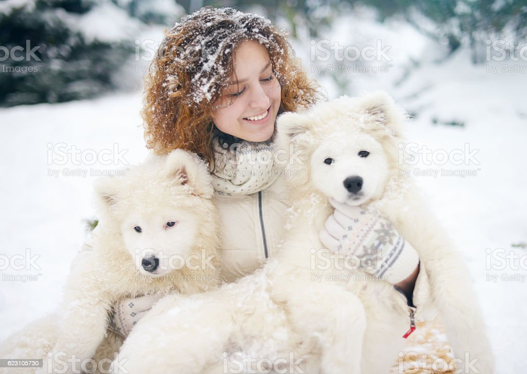 young woman in winter park with white dog stock photo