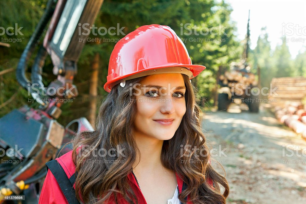 Young woman in work clothes and helmet stock photo