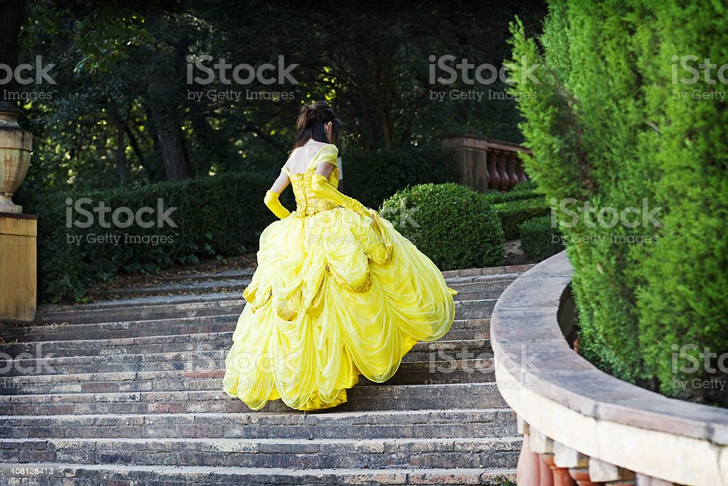 Young Woman in Yellow Dress Running Up Stairs stock photo