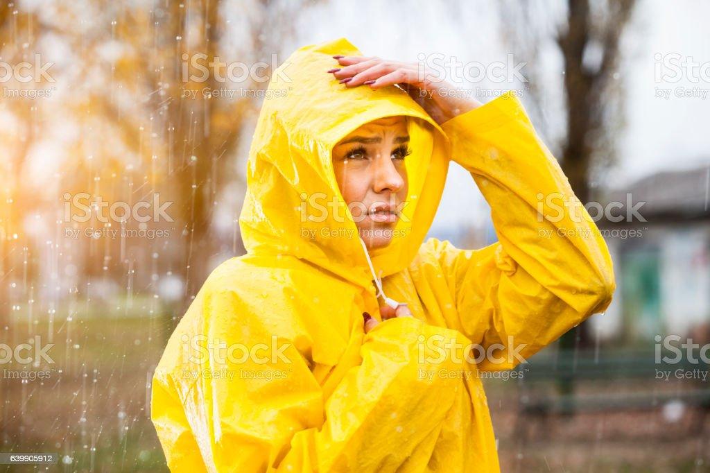 Young woman in yellow raincoat on the rain stock photo