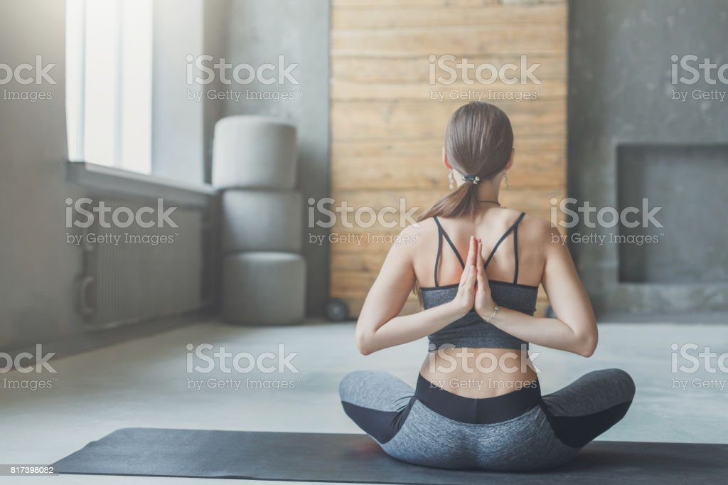 Young woman in yoga class, Reverse Prayer Pose stock photo