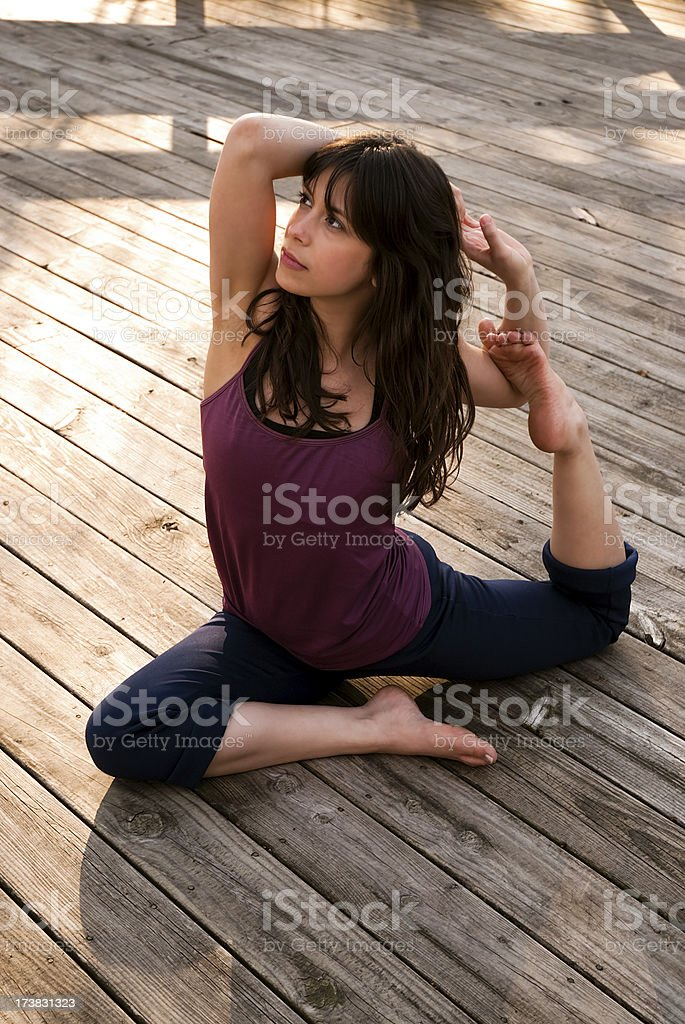 Young woman in Yoga pose outdoors stock photo