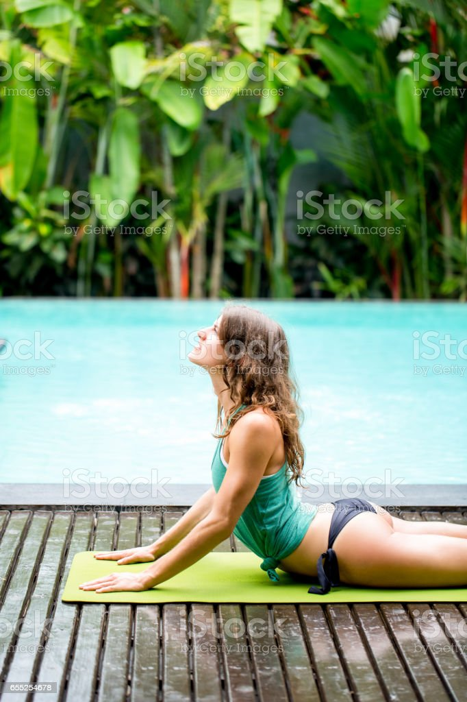 Young woman in yoga pose training outdoors stock photo