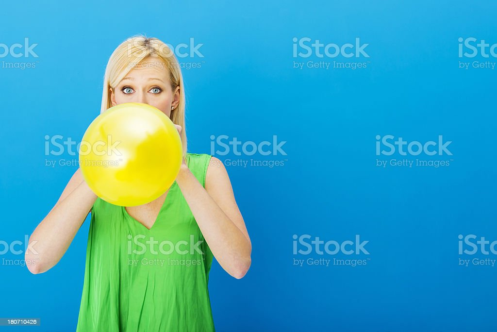 Young woman inflating balloon stock photo