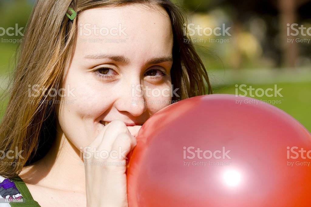 Young woman inflating red balloon royalty-free stock photo
