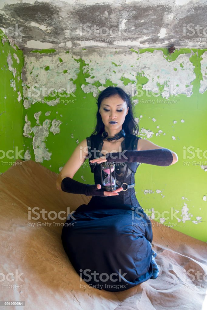 young woman inside an abandoned house with an hourclock waiting stock photo