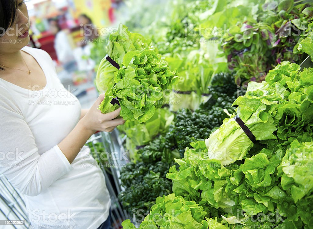 Young woman inspecting the lettuce stock photo