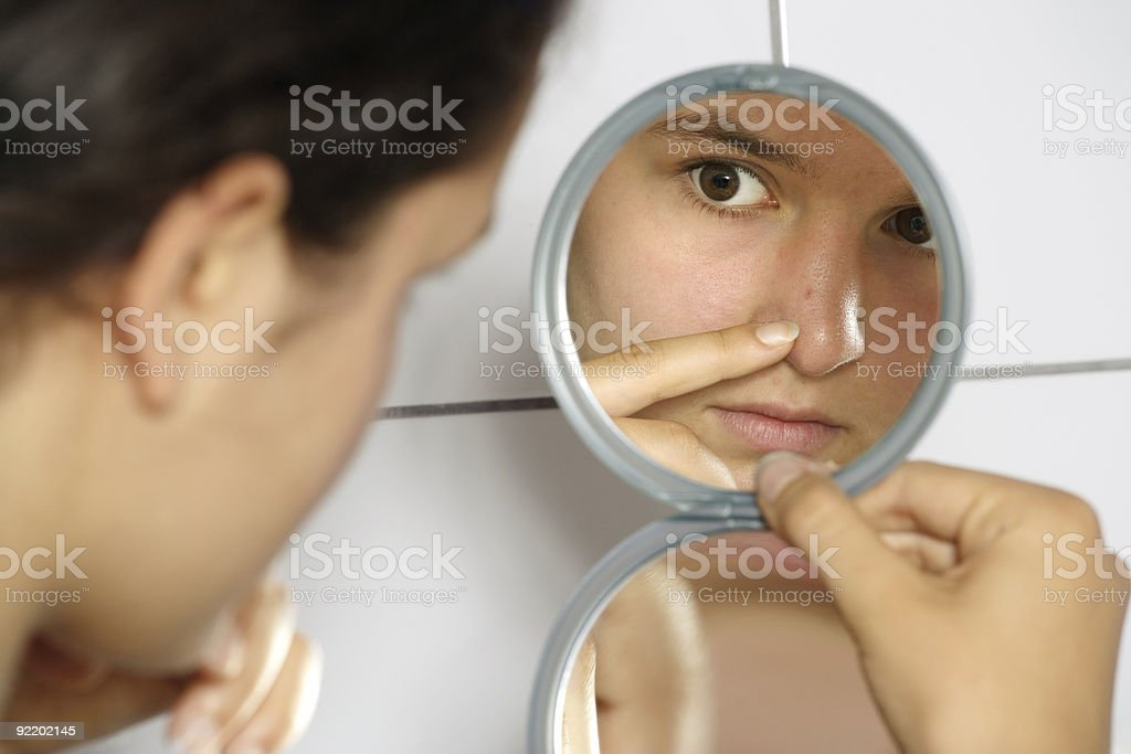 Young woman inspects facial acne in hand mirror royalty-free stock photo
