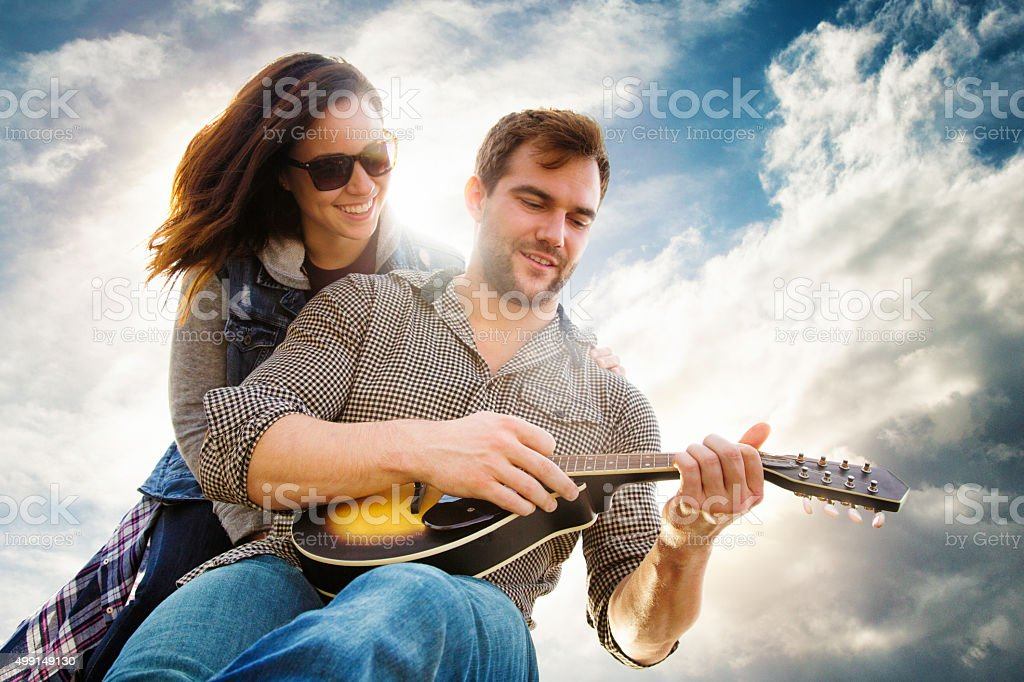 Young woman instructs her boyfriend on chords to play stock photo