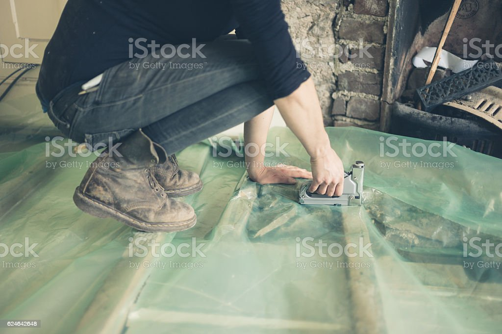 Young woman insulating floor stock photo