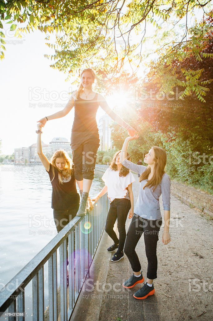 young woman is balancing on a railing on urban background stock photo